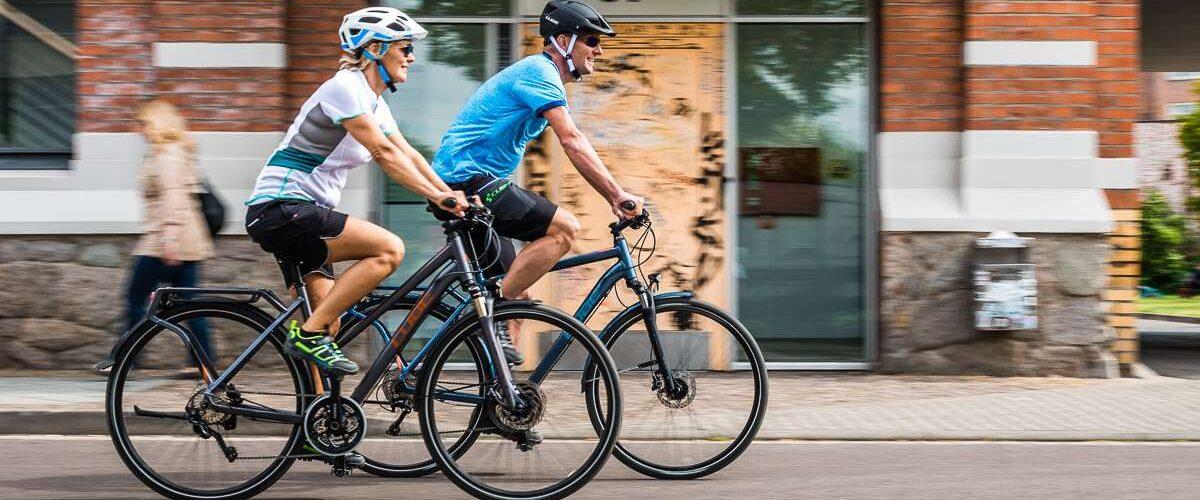 Ein Pärchen fährt auf E-Bikes durch die Stadt.